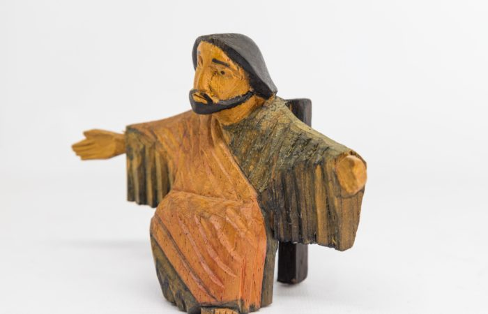 A wooden carving of Jesus with his arms open wide