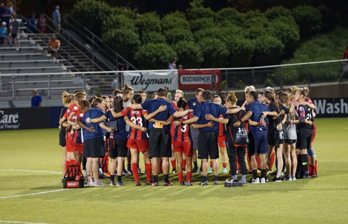 Members of the Washington Spirit women's pro soccer team standing on the field in a large circle with their coaches