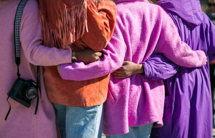 A group of women in pink coats, seen from the back, with arms around each others' waists