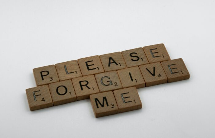 "Scrabble tiles spelling out ""Please forgive me"""