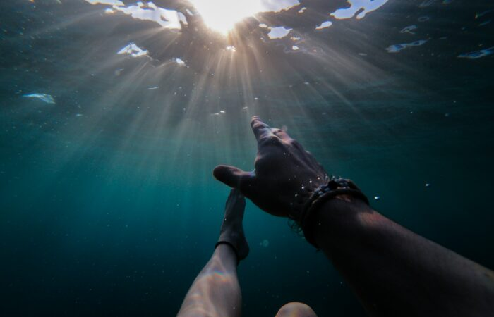 The hands of someone who is swimming underwater, aiming for the sunlight above