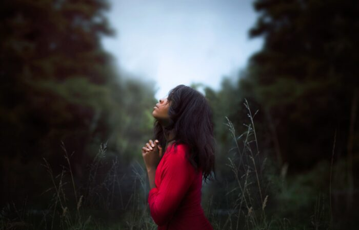 A woman in red praying in the middle of a thick field of grass