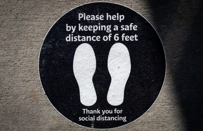 """A black and white sign on the ground that says """"Please help by keeping a safe distance of 6 feet. Thank you for social distancing."""""""