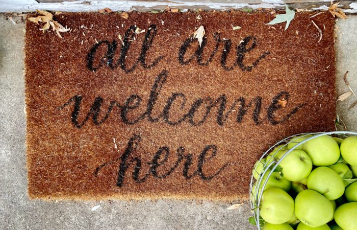 """A welcome mat that says """"All are welcome here"""" with a basket of apples next to it"""
