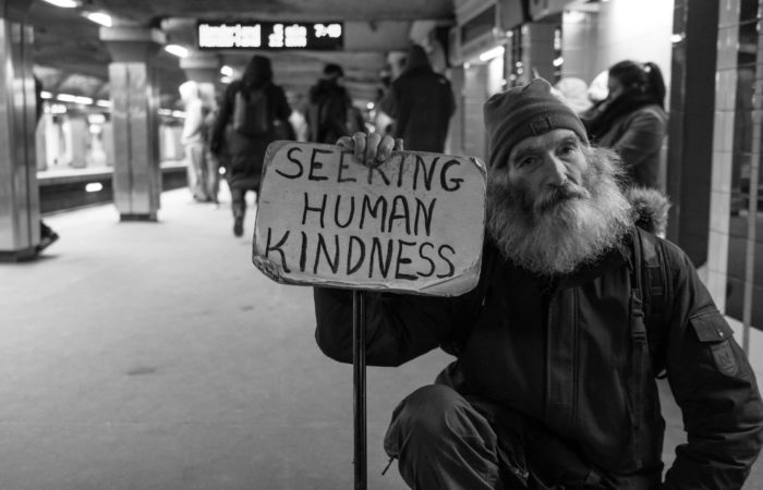"""A black and white picture of a man in a subway holding up a sign saying """"Seeking Human Kindness"""""""