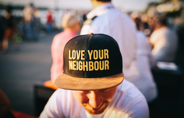 """A man wearing a hat that says """"Love your neighbour"""""""