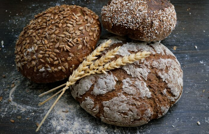 Three loaves of artisan bread and some dried wheat