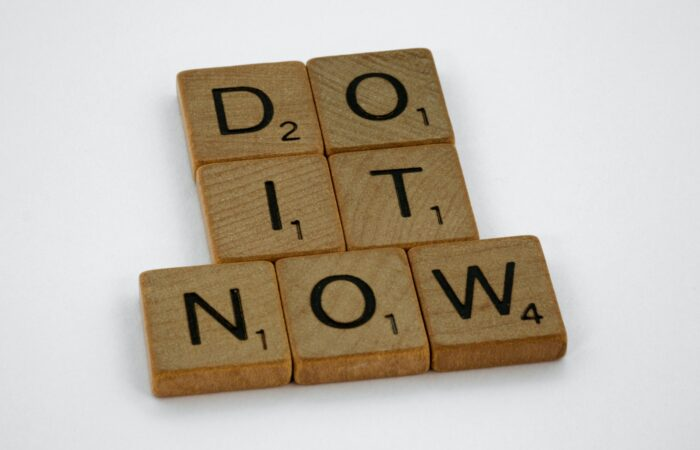 """Scrabble tiles spelling out """"DO IT NOW"""""""