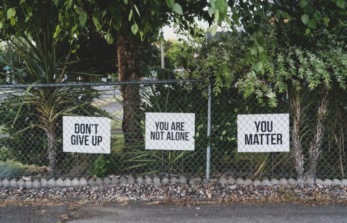 """Signs behind a chain-link fence that say """"DON'T GIVE UP,"""" """"YOU ARE NOT ALONE,"""" """"YOU MATTER"""""""