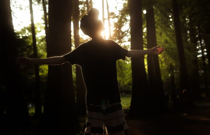 A man standing in a forest opening his arms to brilliant sunlight