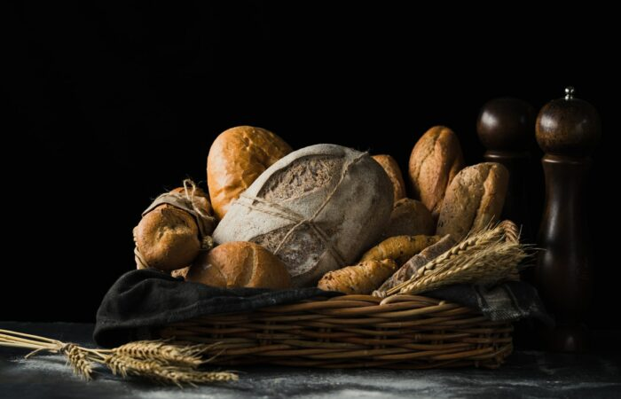 A basket full of many different kinds of bread and a few stems of wheat, with a salt and pepper shaker nearby