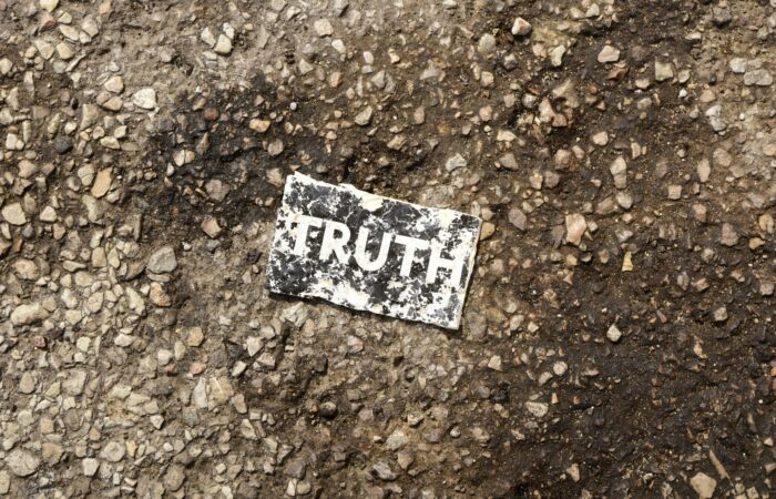 """A piece of paper that says """"TRUTH"""" lying trampled in the mud"""