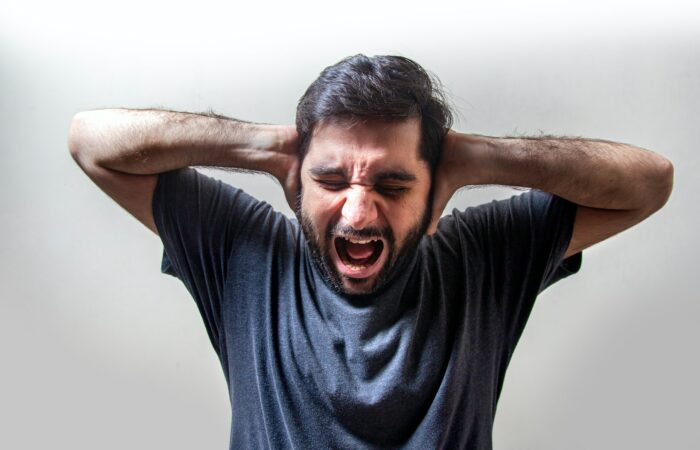 A man screaming and holding his arms to his ears