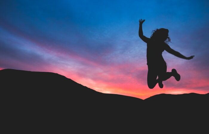 A young woman jumping in the air in front of a hill and a beautiful sunset