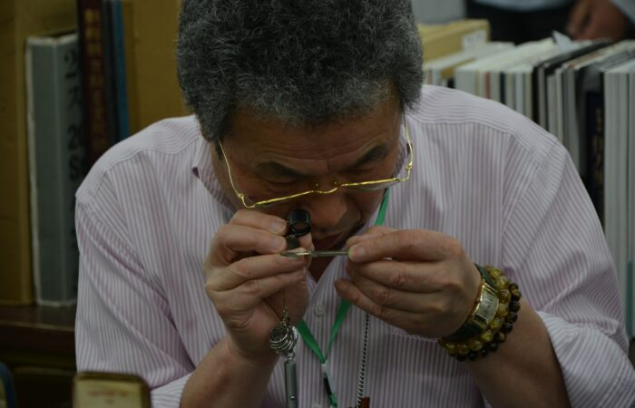 An older man sitting in a library, looking very carefully at an onbject through a magnifying glass
