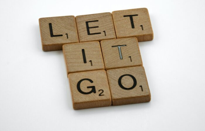 """Scrabble tiles forming the words """"LET IT GO"""""""