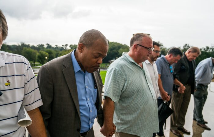 A group of black and white middle-aged men holding hands and praying together