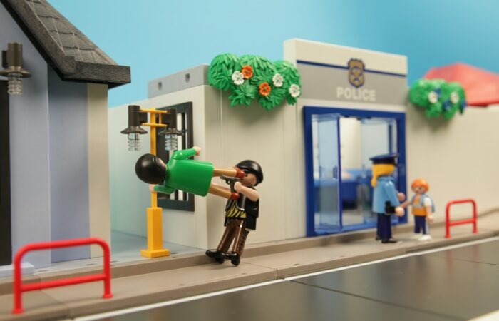 A Playmobil scene which shows a bank and a policeman, with one of the Playmobil people stopping a bank robber.
