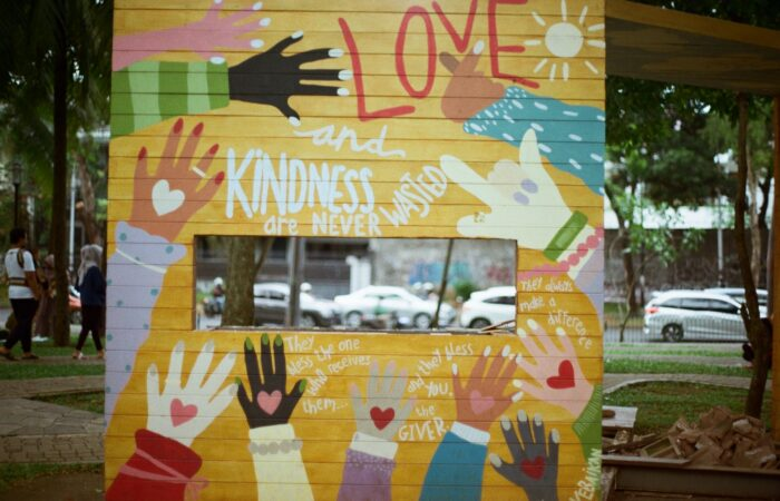"""A freestanding wall with a painting on it of many diverse hands and the slogan """"Love and Kindness are Never Wasted"""""""