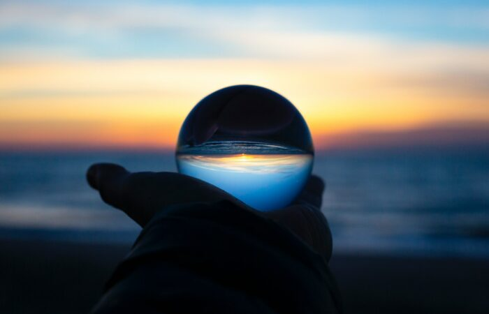 A person watching a sunrise, holding out a glass ball that reflects the sunrise upside down