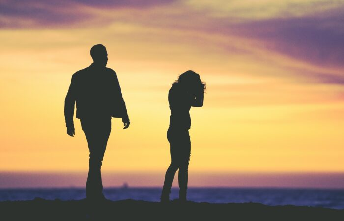 Two people who appear to be upset with each other talking to each other, silhouetted against a sunset on a beach