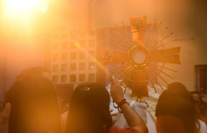 A priest holding up a monstrance to three worshippers, with the sun reflecting brightly off the monstrance