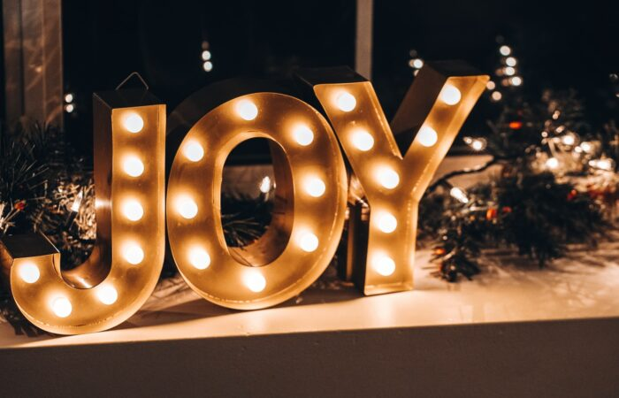 """A light-up sign displaying the word """"JOY"""" in the middle of Christmas decorations of pinecones and holly"""