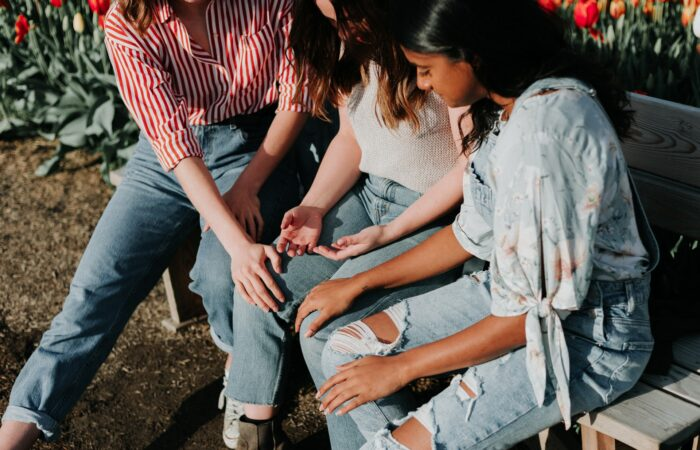 Three girls on a park bench talking and praying together