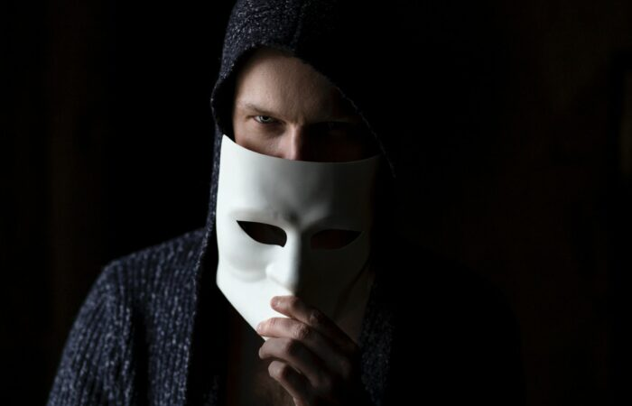 A man with a creepy expression partially hiding in the dark behind a white theater face mask