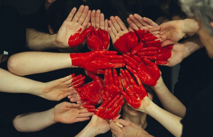 A group of people holding their red-painted hands together to form a heart