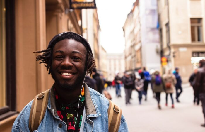 A smiling man with earphones on standing on a city street, with groups of people in the background