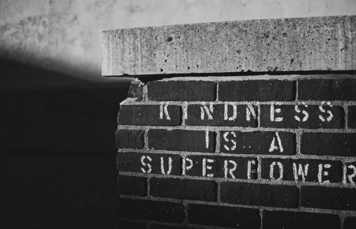 """A black and white image of a brick wall, with """"Kindness is a superpower"""" stenciled on it"""