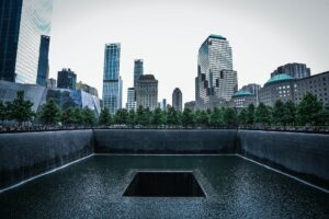 The 9/11 memorial pool with the NYC landscape behind it