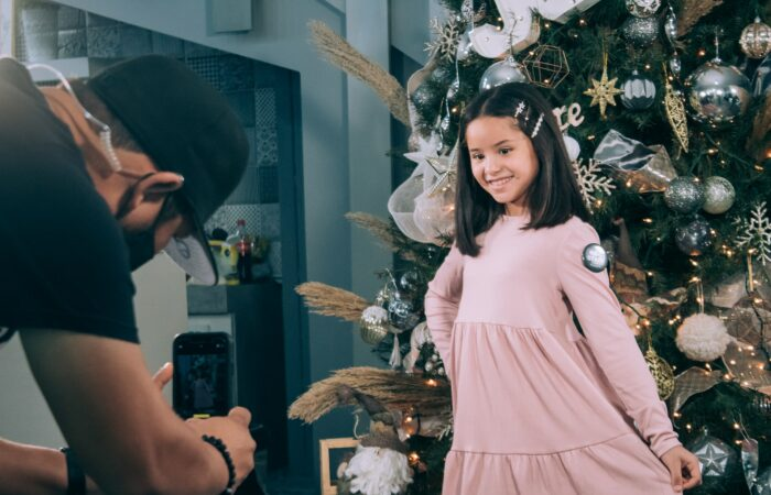 A man taking a picture of his daugther in front of a Christmas tree