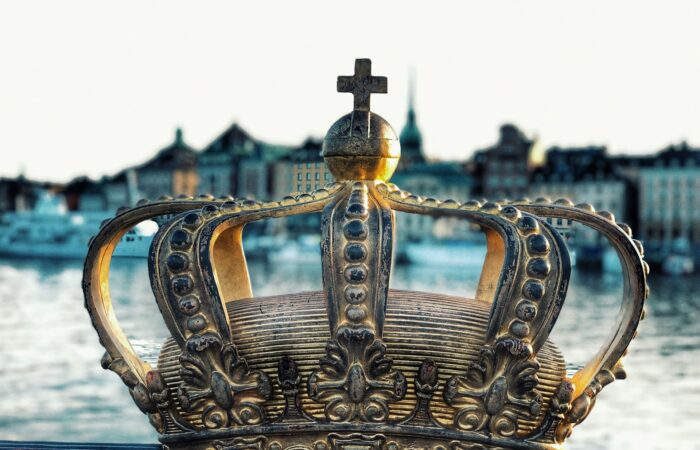 An old, ornate crown seen in closeup against a harbor in Stockholm