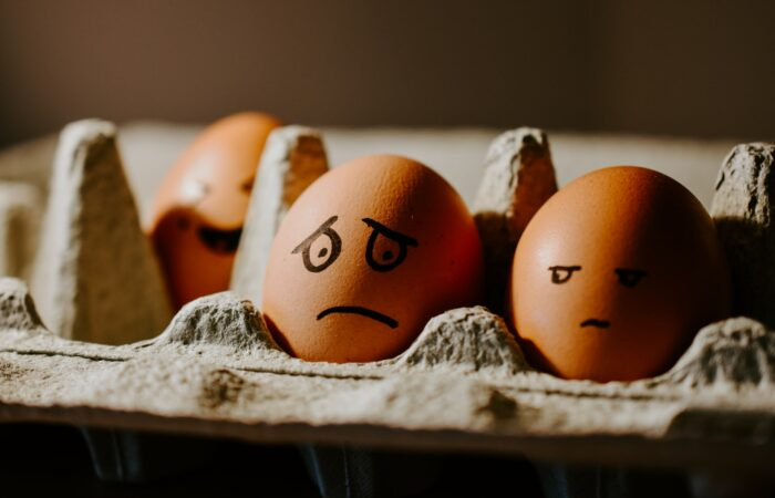 Eggs in a carton, with faces (mostly sad or worried) drawn on them