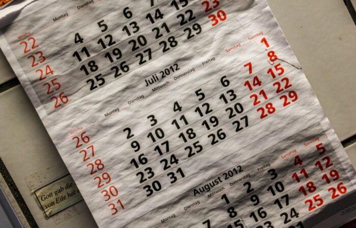 A wet, beaten-up 2012 monthly calendar hanging on a wall