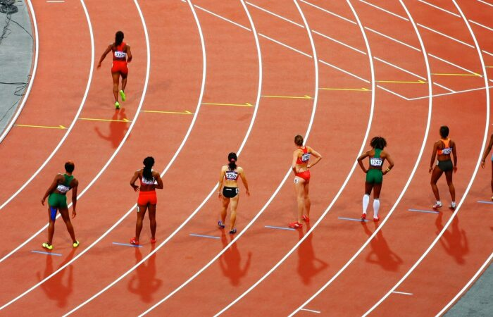 Runners lined up in lanes on a track, with one runner racing ahead