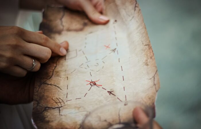 Adult and child hands holding a treasure map