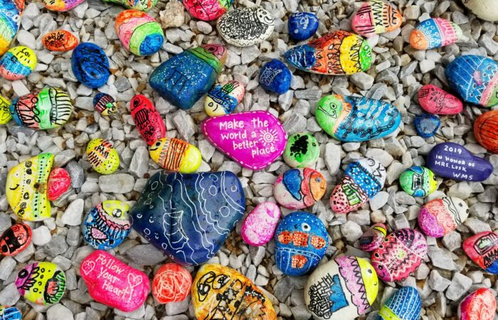 """A number of beautifully colored painted rocks, with one in the middle saying """"Make the world a better place"""""""