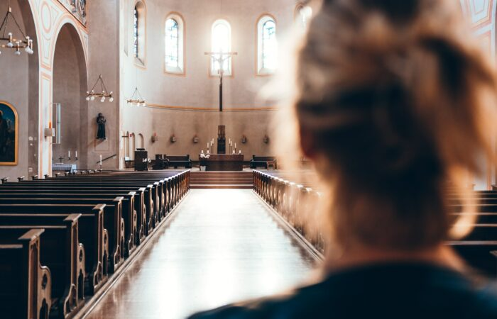 A woman in the back of an empty church looking at the altar