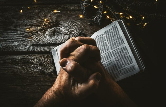 A man's hands folded in prayer on a Bible