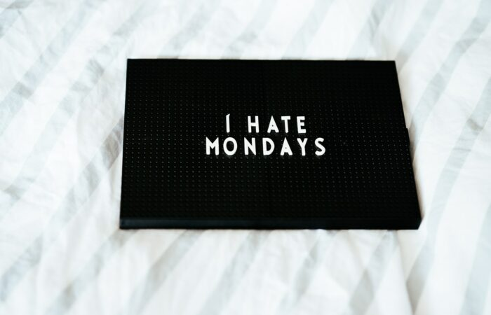 """A plaque that says """"I hate Mondays"""" lying on a bed"""