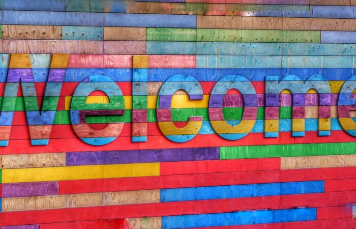"""A brightly colored wooden sign saying """"Welcome"""""""