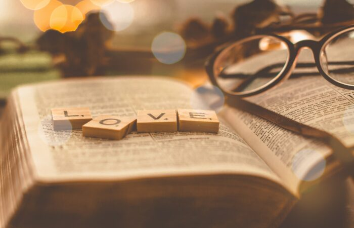A Bible with a pair of glasses and some Scrabble tiles saying LOVE lying on it