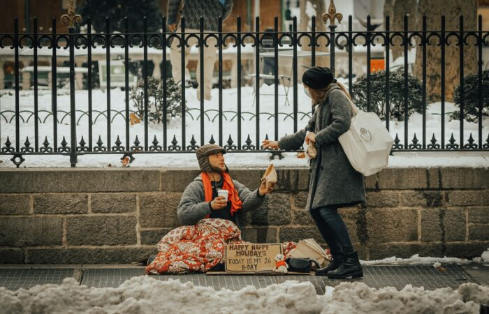 A young woman with a mask on giving some food to a beggar