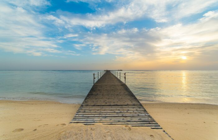 A sandy beach with a wooden walkway reaching out into the ocean