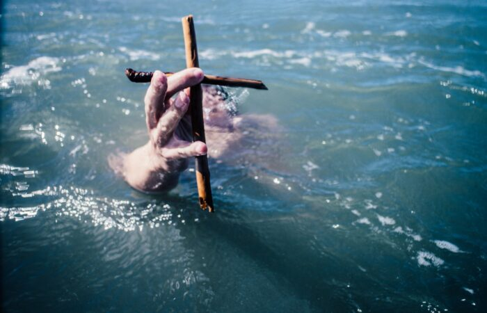 Someone swimming and holding up a cross made of sticks